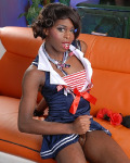 Sexy navy girl Bambie strips naked on an orange sofa and proceeds to pleasure her thick dick